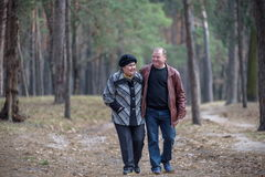 Old couple walking in the forest. Having a good time together. Smiling and talking on autumn or spring Stock Photos