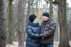 Old couple walking in the forest. Having a good time together. Smiling and talking on autumn or spring Royalty Free Stock Photo