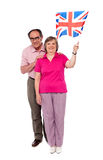 Old couple waving UK flag. Supporting nation Stock Image