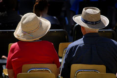 Old Couple Wearing Hats. Old couple sitting in chairs wearing straw hats Royalty Free Stock Photos