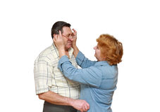 Old couple, wife puts on her husband glasses. Royalty Free Stock Photo