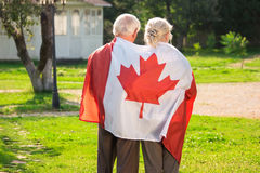 Old couple wrapped in flag. Back view of two people. Life in immigration royalty free stock images