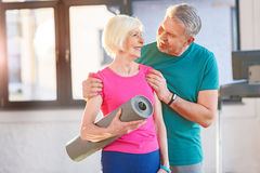 Old couple with yoga mat in fitness class. Happy old couple with yoga mat in fitness class Royalty Free Stock Photos