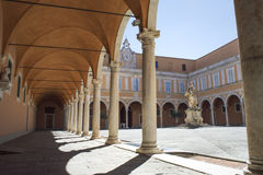 Old courtyard with vaults and a statue, in Pisa, Italy. Royalty Free Stock Photo