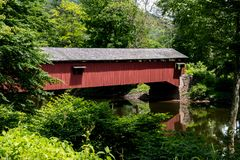 An old covered bridge surrounded by green foliage stock images