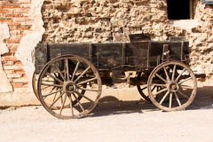 Old covered wagon outside western building Stock Image