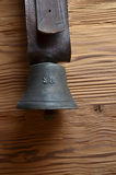 Old cowbell with leather strap on pine wood Royalty Free Stock Photo