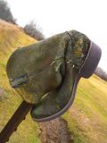 Old cowboy boot on fencepost in an agricultural area Stock Image