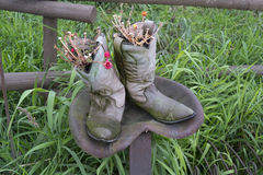 Old cowboy boots with flowers on tractor seat Royalty Free Stock Photography