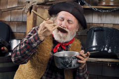 Old cowboy cook tasting food from outdoor kitchen Royalty Free Stock Image