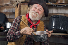 Old cowboy stirs saucepan in outdoor kitchen Stock Images