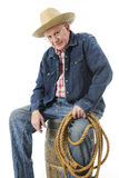 An Old Cowboy Taking a Break. A senior adult cowboy still holding a rope while sitting on an old barrel looking at the viewer.  On a white background Stock Photography