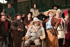 Old Cowboy and Wife. Wheelchair bound cowboy with wife and old west era gang Royalty Free Stock Photos