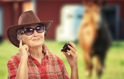 Old cowgirl listening music sites on smartphone Royalty Free Stock Images