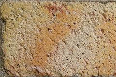 The Cracking Brick Background. Old cracked brick with yellow, salmon and beige colors. Uneven surface. Background. Close up Stock Images