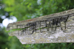 Old Cracked Bridleway Signpost Closeup. Closeup of an old, cracked bridleway signpost pointing down a country lane in England, UK stock photography