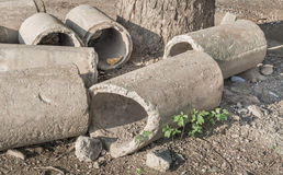 Old and cracked concrete pipe for watering. Stock Photo
