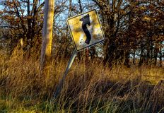 Old and cracked curve ahead sign tilting sideways along a country road in late afternoon with golden sun shinning on it and grass. And utility pole - barbed stock image