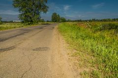 Sunny Cracked Rural Road. Old cracked, damaged asphalt road in countryside at sunny day Stock Photo