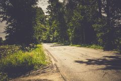 Sunny Cracked Rural Road Filtered. Old cracked, damaged asphalt road in countryside at sunny day, vintage background Royalty Free Stock Image