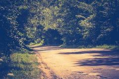 Sunny Cracked Rural Road Filtered. Old cracked, damaged asphalt road in countryside at sunny day, vintage background Stock Image
