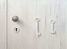 Old cracked gray door with a keyhole decorated with 2 keys Royalty Free Stock Photo