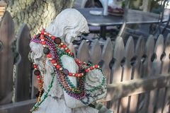 Old cracked mermaid yard art statue draped with Mardi Gras beads in front of blurred wooden picket fence with tree and outdoor. Furniture in the background stock image