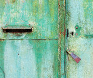 Old cracked metal door with handle and mailbox Royalty Free Stock Photography