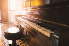 Old and cracked piano and stool with sunlight Royalty Free Stock Images
