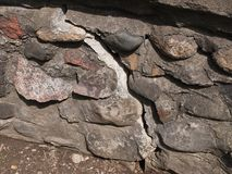 Old cracked stone wall stock photo