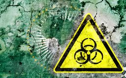 Old cracked wall with biohazard warning sign and painted flag Royalty Free Stock Image