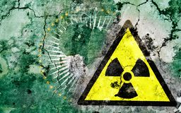 Old cracked wall with radiation warning sign and painted flag Royalty Free Stock Photography