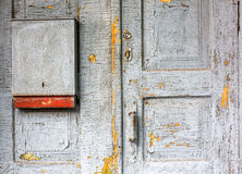 Old cracked wooden door with handle and mailbox Royalty Free Stock Photo