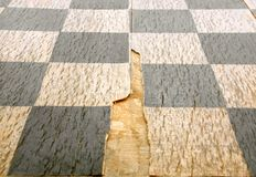 Old crackled chessboard. For backgrounds or textures Stock Image