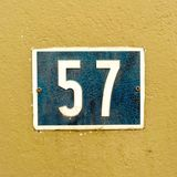 House number 57. Old, crackled house  number fifty seven 57 on a plastered wall Royalty Free Stock Image