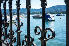 Old craftet iron fence with lake view and boat Stock Image