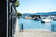 Old craftet iron fence with lake view and boat Stock Photography