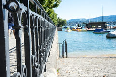 Old craftet iron fence with lake view and boat Stock Photos