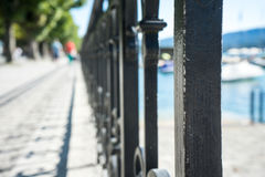 Old craftet iron fence with lake view and boat Stock Photo