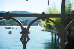 Old craftet iron fence with lake view and boat Royalty Free Stock Images