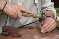 Old craftsman Mason during the processing of a copper with an en. Graver and hammer royalty free stock images
