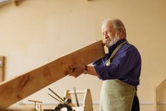 Old craftsperson is working with timber indoors. Old attractive craftsperson is working with timber indoors. woodworking concept stock image