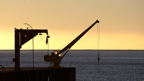 Old crane on the dock in the sunset on a pier of Chile Stock Image