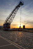Old crane at Duisburg Inner Harbor. Sunset behind old crane at Duisburg Inner Harbor Stock Image