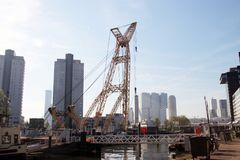 Old crane in harbor named Leuvehaven in downtwon Rotterdam on sunny day Stock Photo