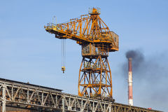 Old crane and smoky chimney Royalty Free Stock Image