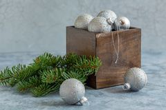 Christmas silver balls in an old wooden box. Old crate with silver Christmas balls and fir branch on textured concrete background royalty free stock photo
