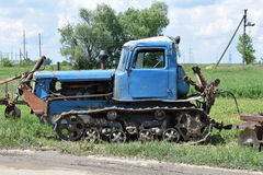 Old crawler tractor standing in a field Royalty Free Stock Images