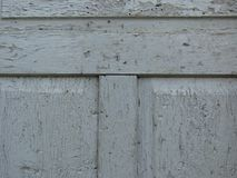 Old crecked grey wooden door board eaten by worms and beetles. Peeled grey paint. Old crecked grey wooden door board eaten by worms and beetles. Suitable for royalty free stock image