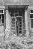 Old, creepy, abandoned building doorway. Old, creepy, abandoned building. Falling apart with shattered windows. Black and white Stock Photo